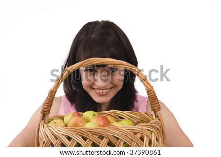 Girl in pink dress is holding a basket full apples on white background.  Beautiful girl holding a basket of delicious fresh fruits. Isolated over white. - stock photo