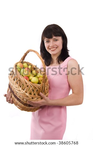 Girl in pink dress is standing and holding a basket full apples on white background. Beautiful girl holding a basket of delicious fresh fruits.