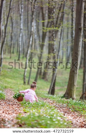 Girl in pink dress picks up flowers in forest
