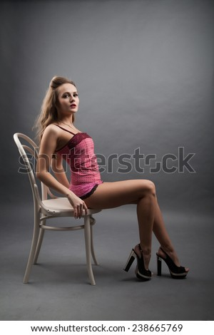 Girl in pink lingerie sitting on a chair