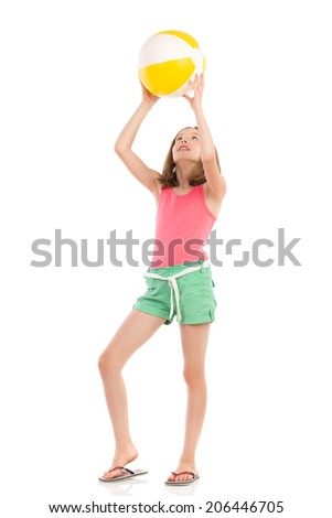 Girl in pink shirt and green shorts is playing beach ball. Full length studio shot isolated on white. - stock photo