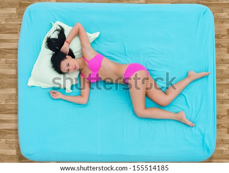 Girl in pink underclothes lying in bed, view from above - stock photo