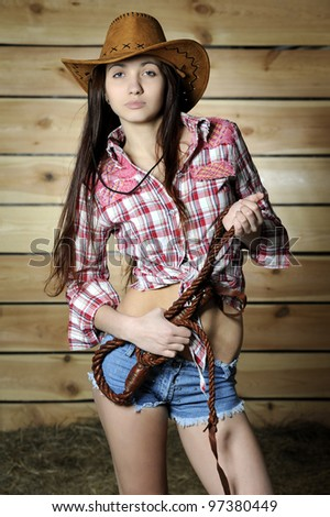 Girl in plaid shirt and cowboy hat with whip against wooden wall - stock photo