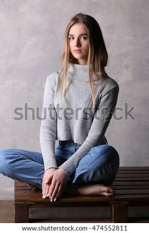 Girl in pullover sitting on a deck. Gray background