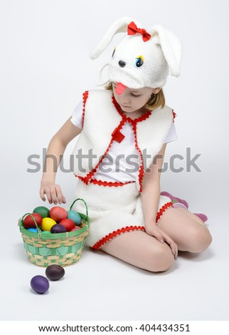 Girl in rabbit costume with a basket of Easter eggs on a white background
