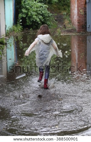 girl in raincoat and rubber boots running through a puddle