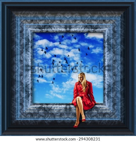 girl in red coat sitting on the edge of a picture frame with birds flying over a blue sky - stock photo