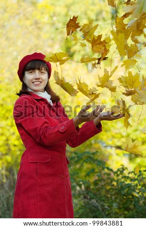 Girl in red coat throw up maple leaves - stock photo