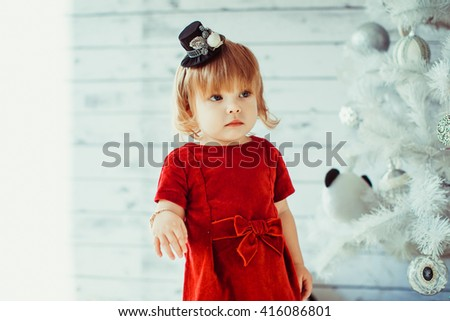 girl in red dress at the Christmas tree - stock photo