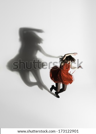 Girl in red dress dancing with a shadow - stock photo