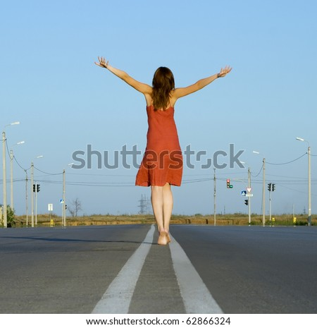 girl in red dress walk barefoot on empty road - stock photo