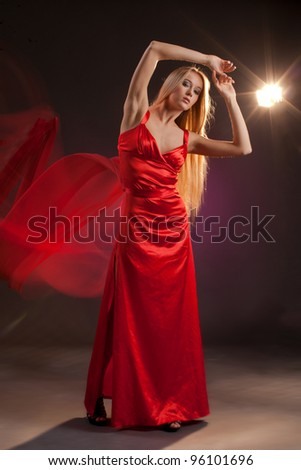 girl in red dress with a train of flying on a dark background with backlit