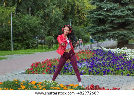 Girl in red jacket listening to music streaming with headphones and dancing in park.