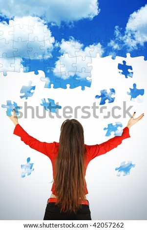 Girl in red with blue sky above. Sky is puzzle textured and part of sky falling to girl's hands