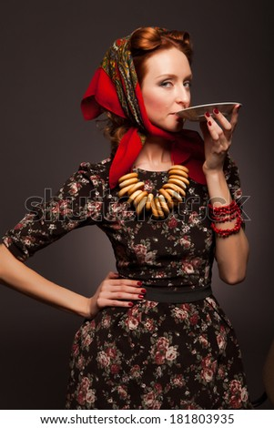 Girl in Russian style posing in red kerchief and bagels on the neck.  Drinking tea from a saucer.