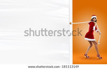 Girl in Santa costume pulling white blank banner. Place for text