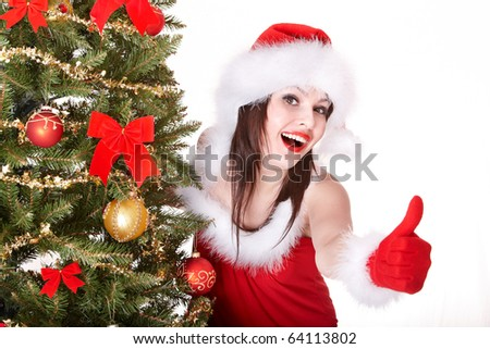 Girl in santa hat are showing thumb  near christmas tree.  Isolated. - stock photo