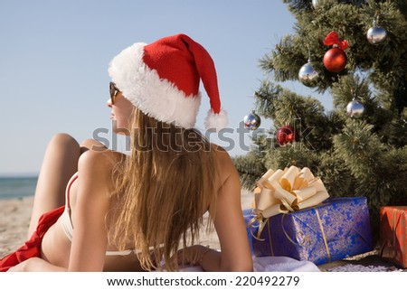 Girl in santa hat enjoying the sun while lying on the beach near the Christmas tree decoration balls - stock photo