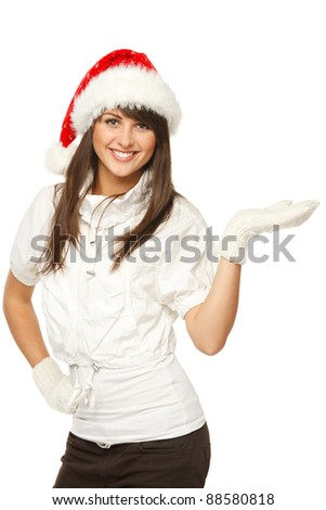 Girl in Santa hat showing a product - empty copy space on the open hand palms, over white background - stock photo