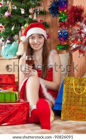 Girl in Santa hat sits with wine - stock photo