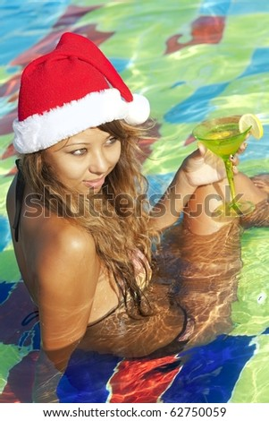 Girl in Santa hat sitting in the swimming pool with martini glass - stock photo