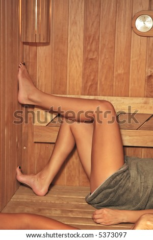 Girl in sauna with legs up.