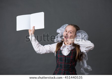 Girl in school uniform indicates a notebook - stock photo