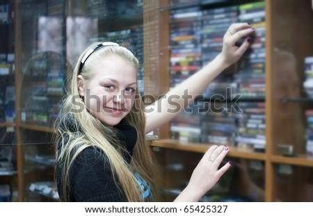 Girl in shop chooses CD or DVD disk - stock photo