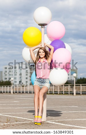 girl in short jeans shorts, sleeveless striped top and high heels leans on light-pole holding bunch of multicolored balloons in bright summer day - stock photo
