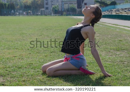 girl in shorts and t-shirt doing exercises on the pitch