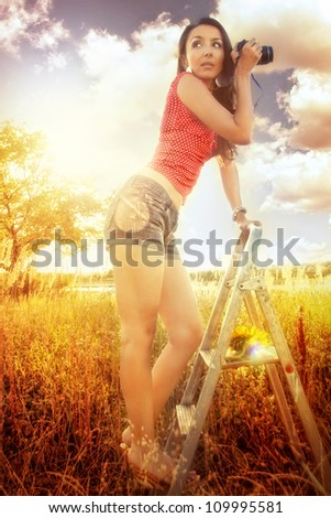 Girl in shorts at sunflowers field holding photo camera - stock photo