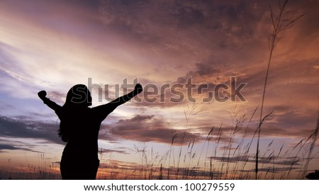Girl in silhouette with open arms freedom feeling over sunset background - stock photo