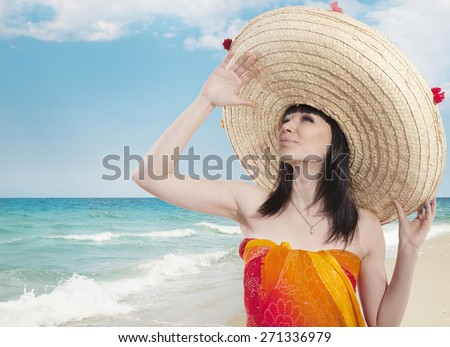 Girl in sombrero and sarongs on the sea background - stock photo