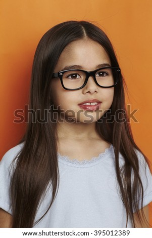 Girl in spectacles against orange background