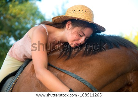 Girl in straw hat hugs her horse - stock photo