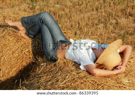 Girl in straw hat lies on bales of straw at field