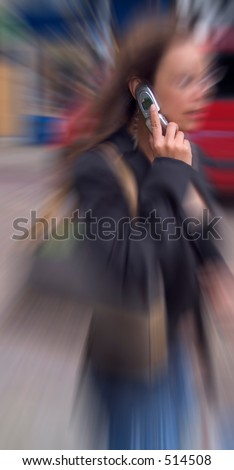 Girl in street on mobile phone, zoom blur to hand, phone and ear. - stock photo