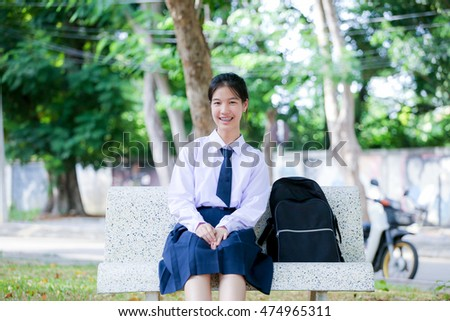 girl in student uniform sitting at the park