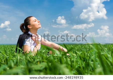 girl in suit resting in a field - stock photo