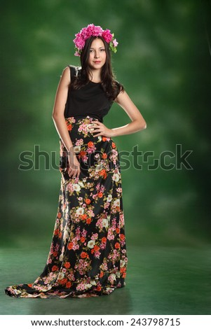 Girl in suit summer. long beautiful hair. on the head a crown of flowers. long dress with flowers - stock photo