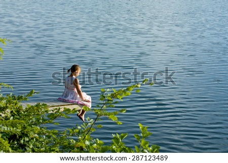 Girl in summer dress sitting at deck looking over water - stock photo