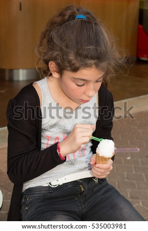 girl in summer holidays eating ice candy on the street