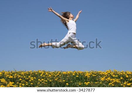 Girl in summer white clothes flying in a jump over flowering dandelion field. - stock photo