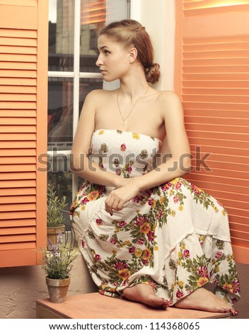 Girl in sundress sitting and looking out the window near the orange shutters