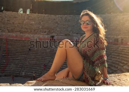 girl in sunglasses at sunset in Aspendos amphitheatre, Antalya, Turkey - stock photo