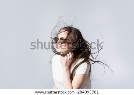 Girl in sunglasses hair in a high wind