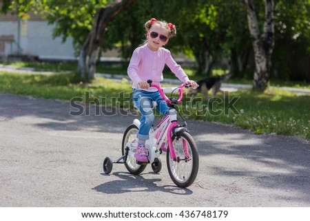 girl in sunglasses riding on a bicycle summer sunny day  - stock photo