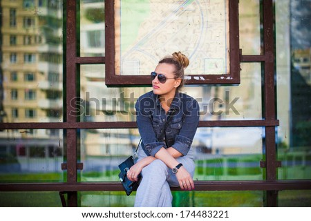 Girl in sunglasses waiting at the bus stop - stock photo