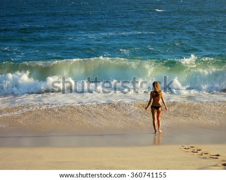 Girl in swimming suit standind at the ocean beach with wave - stock photo