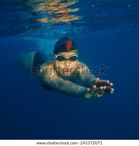 Girl in swimsuit underwater. Front view - stock photo